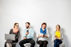 People with gadgets on the white background. People in colorful casual clothes using gadgets sitting in a row on the white wall background stock photography