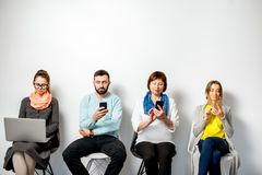 People with gadgets on the white background. People in colorful casual clothes using gadgets sitting in a row on the white wall background Stock Photos
