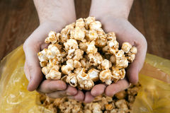 People gaining a bunch of popcorn from the package. Close up royalty free stock images