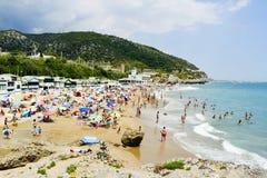 People at the Garraf Beach in Sitges, Spain. SITGES, SPAIN - JULY 9, 2017: People enjoying, relaxing, sunbathing or bathing at the Garraf Beach in Sitges, a Stock Photos