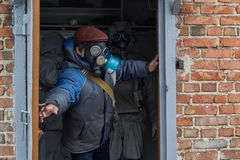 People in gas masks and protective suits are saved in a bunker during a chemical hazard. Chemical Hazards stock photos