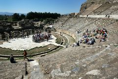 People gather amongst the Roman theatre ruins at the ancient site of Ephesus in Turkey. Stock Photography