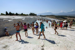 People gather around the thermal pools at the travertines, or Cotton Castle, at Pamukkale in Turkey. People stand in one of the thermal pools at the travertines stock images