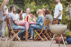 People gathered around a wooden table, eating, drinking and having fun during a grill party on the terrace. stock images