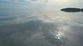 People Gathering Sea Shells at Shallow Water with Reflecting Surface. Aerial View stock video footage