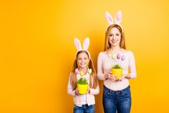 People gatherings family concept. Portrait of childish adorable. Sweet playful tender gentle mom and preteen girl holding two hand-crafted vases with dotted Stock Image
