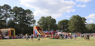 People at the Germantown, TN Annual Festival 2017. A children`s play area with jumpy houses, slides and kiddie rides at the Annual Germantown, TN Festival in Royalty Free Stock Photography