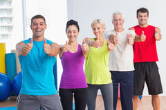 People gesturing thumbs up at gym. Portrait of cheerful men and women gesturing thumbs up at gym Stock Image