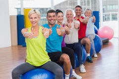 People gesturing thumbs up in health club. Portrait of smiling people sitting on exercising balls gesturing thumbs up in health club Royalty Free Stock Image