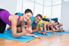 People gesturing thumbs up while lying on exercise mats. Portrait of happy people gesturing thumbs up while lying on exercise mats at gym Royalty Free Stock Images