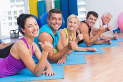People gesturing thumbs up while lying on mats at gym Royalty Free Stock Photography