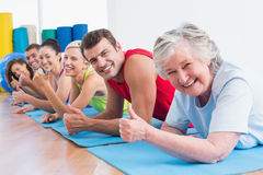 People gesturing thumbs up while lying on mats at gym Royalty Free Stock Images
