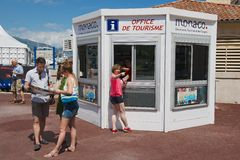 People get maps and directions at the office of tourism booth in Monaco. Stock Images