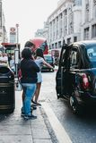 People getting on a black cab on Oxford Street, London, UK. People getting on a black cab on Oxford Street, a major road in the City of Westminster in the West stock photos