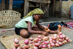 People in GHANA. ACCRA, GHANA - MARCH 4, 2012: Unidentified Ghanaian woman sells onion in the street in Ghana. People of Ghana suffer of poverty due to the stock images