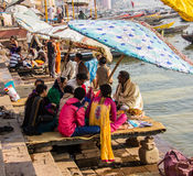 People on the ghats of Varanasi. People sitting on the holy ghats of the ancient hindu city of Varanasi, looking at the holy river Ganges Royalty Free Stock Image