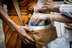 People give alms food and item offering to Buddhist monk Royalty Free Stock Photo
