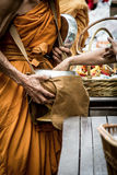People give alms food and item offering to Buddhist monk Stock Image