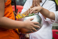 People give alms to a Buddhist monk at temple Stock Images