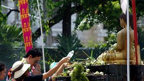 People give the flowers to Buddha statue. Chiang Mai, Thailand - APRIL 13, 2015: people give the flowers to Buddha statue and spray holy water to the statue on stock video