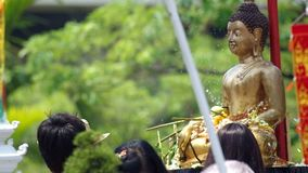 People give the flowers to Buddha statue. Chiang Mai, Thailand - APRIL 13, 2015: people give the flowers to Buddha statue and spray holy water to the statue on stock footage