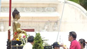 People give the flowers to Buddha statue. Chiang Mai, Thailand - APRIL 13, 2015: people give the flowers to Buddha statue and spray holy water to the statue on stock video footage