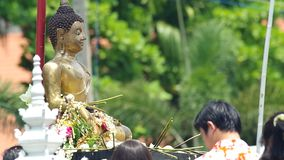 People give the flowers to Buddha statue and spray holy water stock video footage