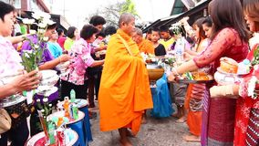 People give food offerings to a Buddhist monk in Morning stock video