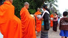 People give food offerings to a Buddhist monk in Morning stock footage
