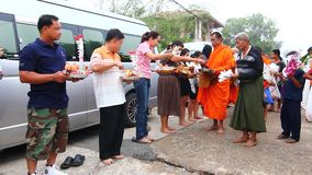 People give food offerings to a Buddhist monk in Morning stock video footage