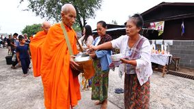 People, give food offerings to a Buddhist monk in Morning stock video