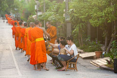 People giving alms to buddhist monks on the street, Laos Stock Image
