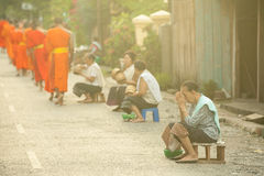 People giving alms to buddhist monks on the street, Laos Royalty Free Stock Photography