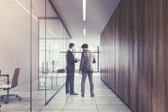 People in a glass and wooden office corridor Royalty Free Stock Images
