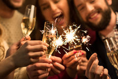 People with glasses of champagne and sparklers. Close-up view of happy people with glasses of champagne and sparklers Stock Image