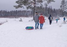 People go with accessories for a winter toboggan run in the snow. Winter fun stock image