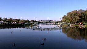 People go across bridge near fountains in park in summer Moscow. stock footage