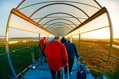 People  go through a covered walkway to the plane Stock Images