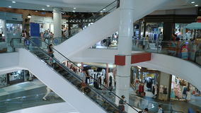 People go down the escalator at mall stock video