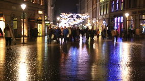 People go on evening street of Krakow decorated by Christmas stock video