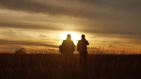 People go group travel of tourists field nature of a sunset silhouette two people travel. tourists nature people group. People go group travel tourists field stock footage