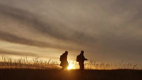 People go group travel of tourists field nature of a sunset silhouette two travel people . tourists nature lifestyle. People go group travel tourists field stock video footage
