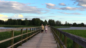 People go long wooden bridge across lake, evening sky light wind stock video footage