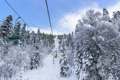 People go on the old two-seat cable car second stage to the ski slopes. The road is laid in a snow-covered fir forest. Cloudy stock photos