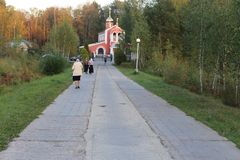 People go to an orthodox temple in the background of the forest.  Royalty Free Stock Photos