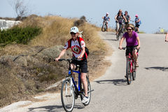 People going by bike in the city in Milos, Greece. A lot of tou Stock Images