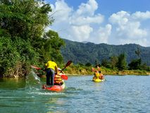 People going down Nam Song River in kayaks near Vang Vieng, Vien. Tiane Province, Laos. Kayaking is a popular tourist activity in Vang Vieng royalty free stock image