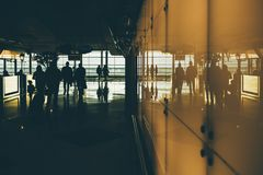 People going inside mall or airport terminal. Silhouettes of going people inside of dark interior of contemporary airport terminal or railroad depot station, or Royalty Free Stock Photo