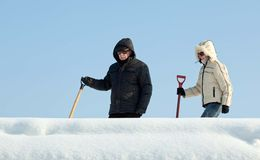 People going to remove snow from a roof Royalty Free Stock Photos