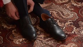 People going to work, man tying laces on black leather shoes. stock video footage